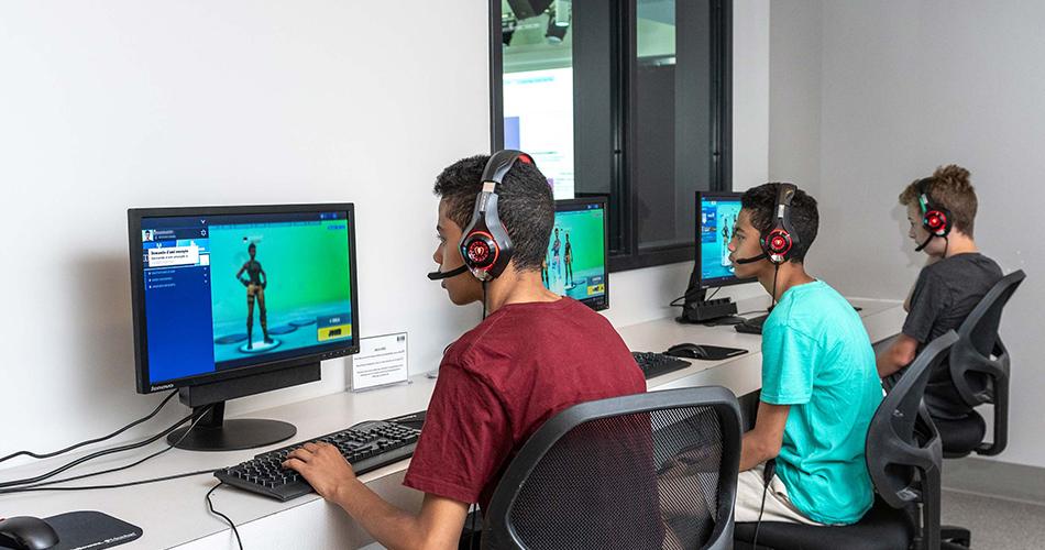 Trois jeunes garçons jouant à un jeu en ligne sur leur ordinateur