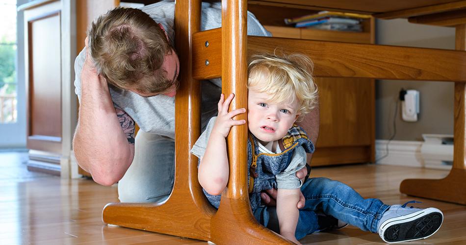 Homme et enfant réfugiés sous une table