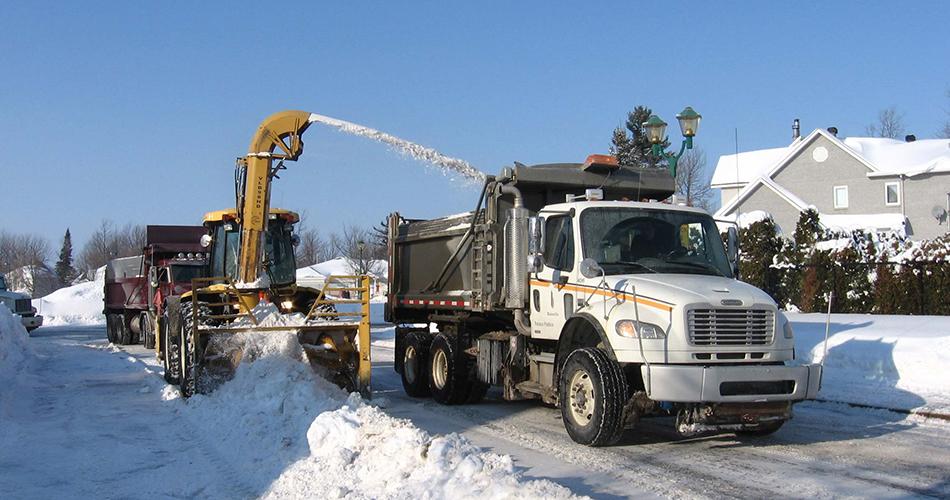 Souffleuse qui souffle de la neige dans un camion