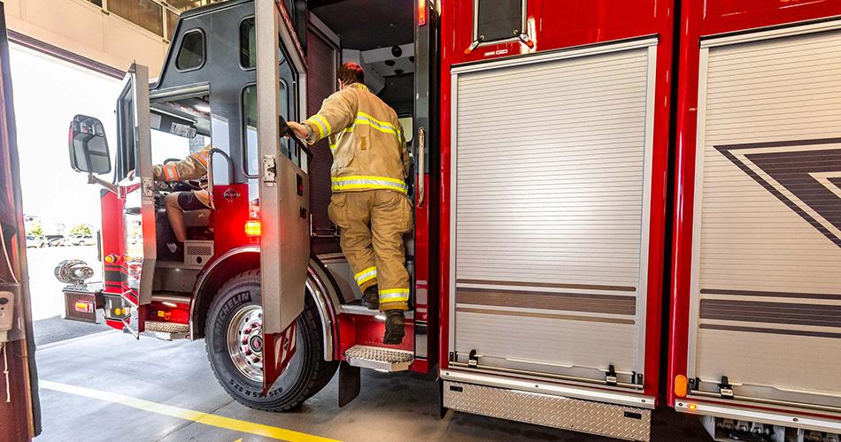 Deux pompiers qui embarquent dans un camion