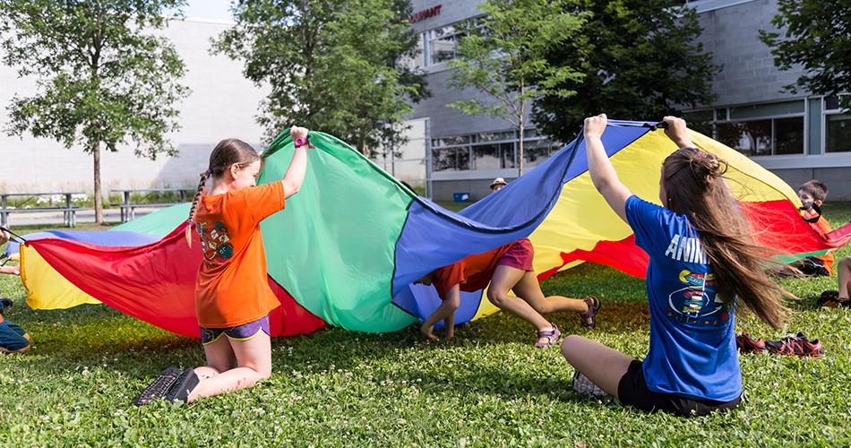 Animatrice avec enfants jouant avec un parachute